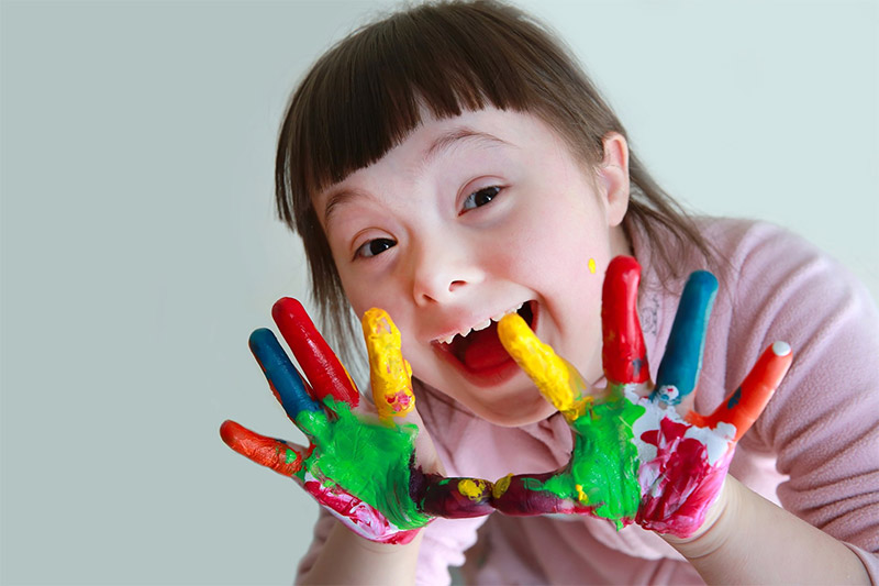 little girl with hands covered in paint