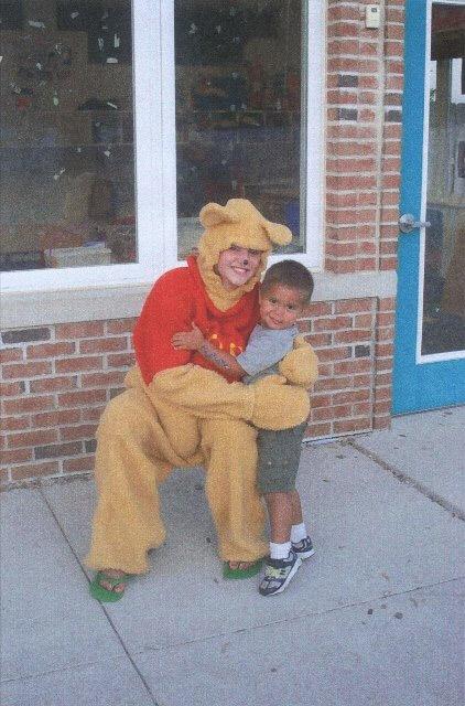 Pooh Bear hugging little boy